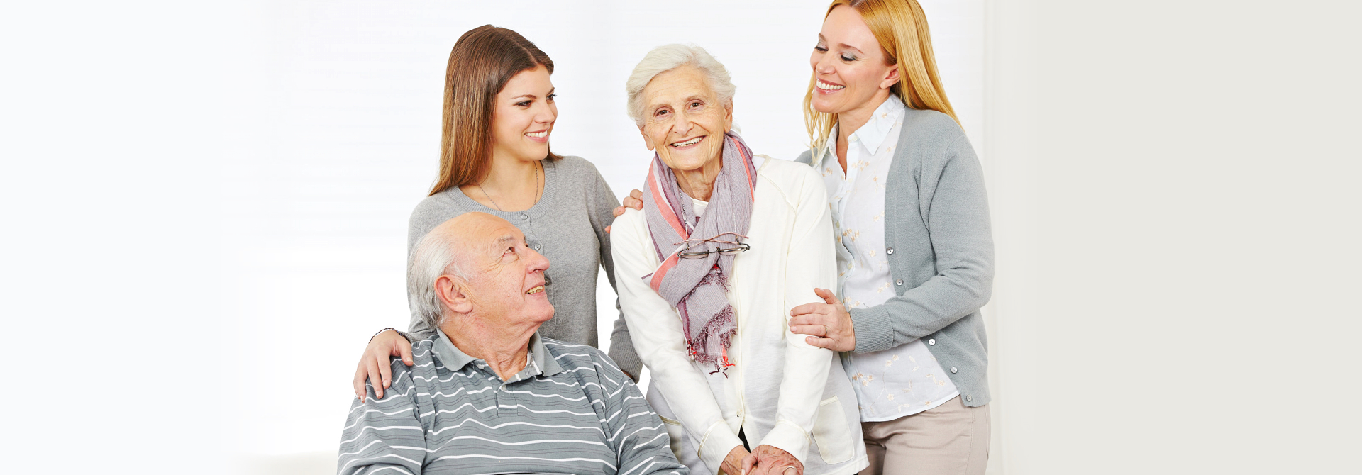 two caregivers and senior couple smiling