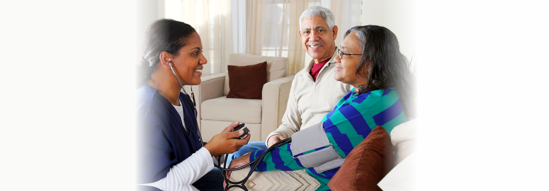 caregiver checking blood pressure of the old woman